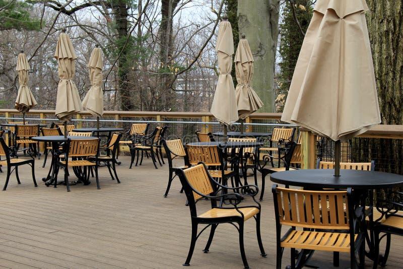 Scène paisible des tables et des chaises avec les parapluies attachés sur le patio extérieur de restaurant images stock