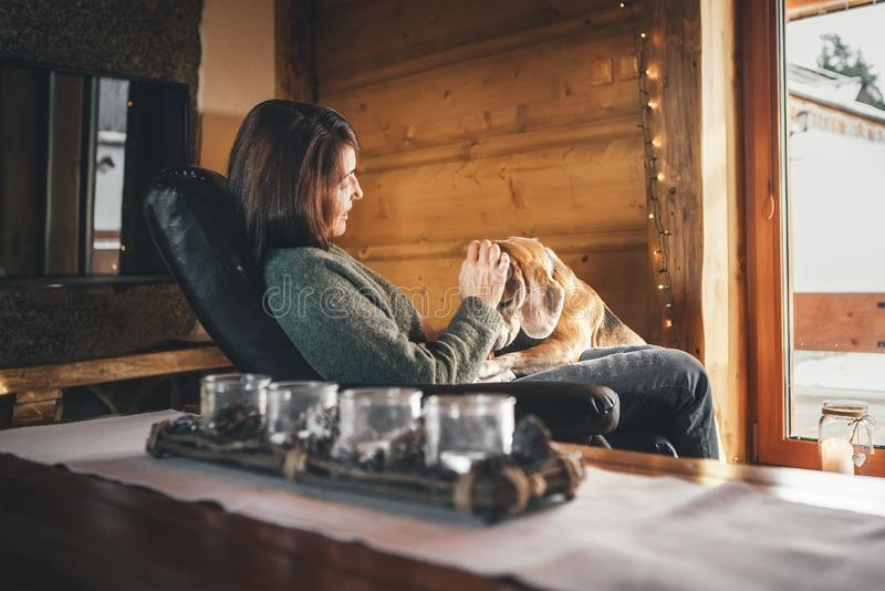 Scène tendre avec la femme et son chien de briquet dans la chaise confortable vis-à-vis de la grande fenêtre dans la maison confo photo libre de droits
