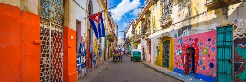 Scène urbaine avec un drapeau cubain sur une rue colorée à La Havane images libres de droits