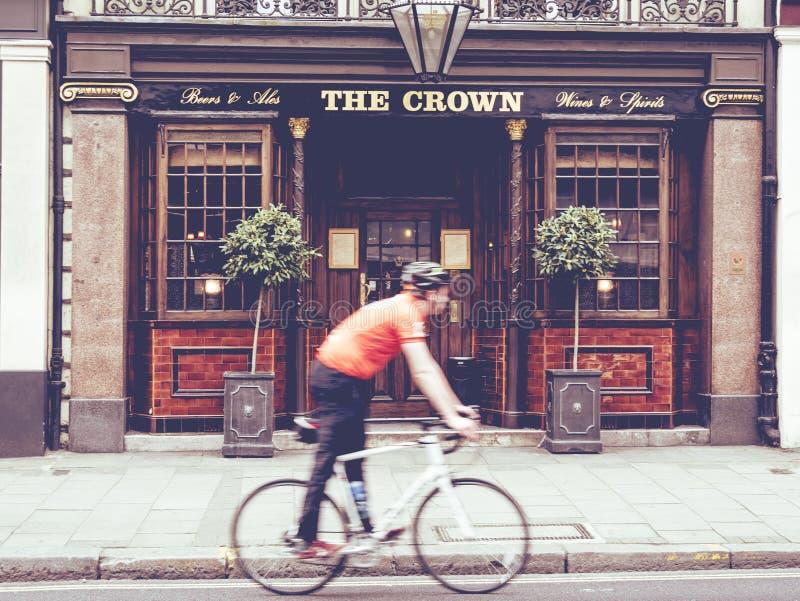 Scène urbaine d'un cycliste marchant devant un bar anglais images stock