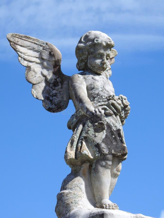 Sc?ne dans un cimeti?re : plan rapproch? d'une vieille statue en pierre d'un petit ange photo stock