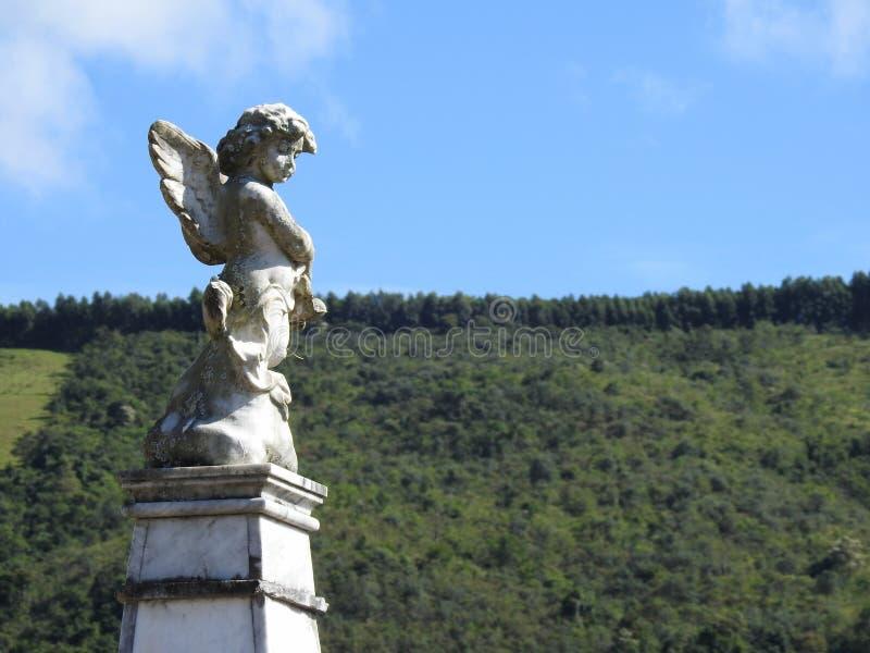 Sc?ne dans un cimeti?re : une vieille statue en pierre d'un petit ange ? l'arri?re-plan, au ciel bleu, aux nuages et ? la v?g?tat images libres de droits