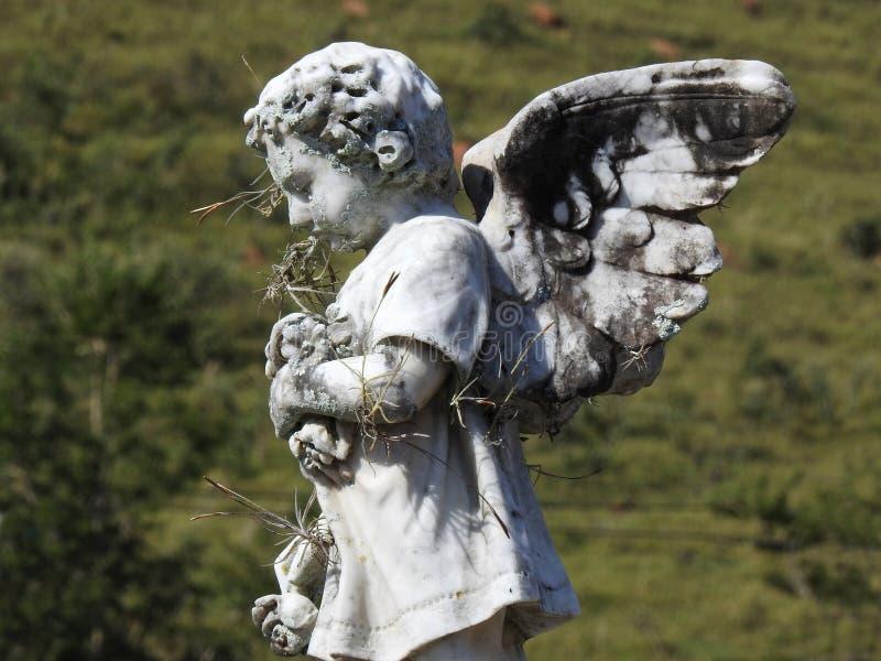 Sc?ne dans un cimeti?re : une vieille statue en pierre d'un petit ange tenant quelques fleurs photos stock
