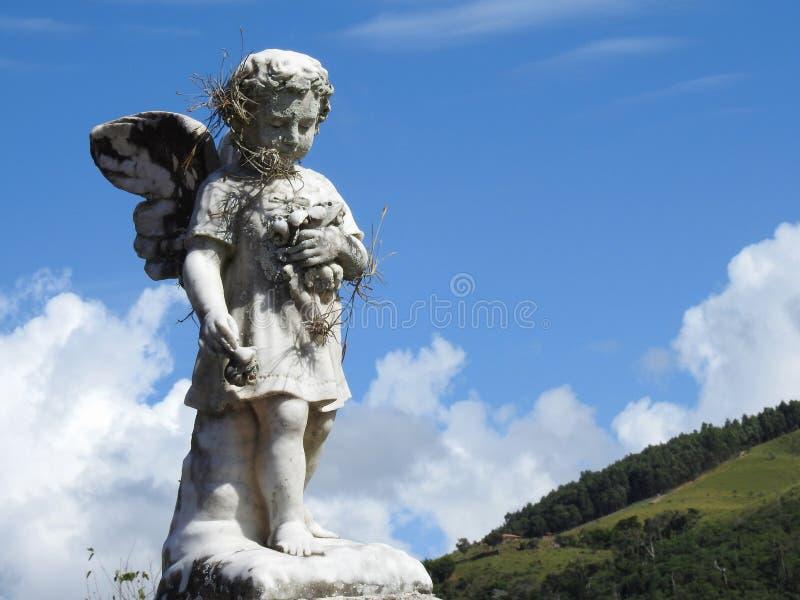 Sc?ne dans un cimeti?re : une vieille statue en pierre d'un petit ange tenant quelques fleurs photographie stock libre de droits