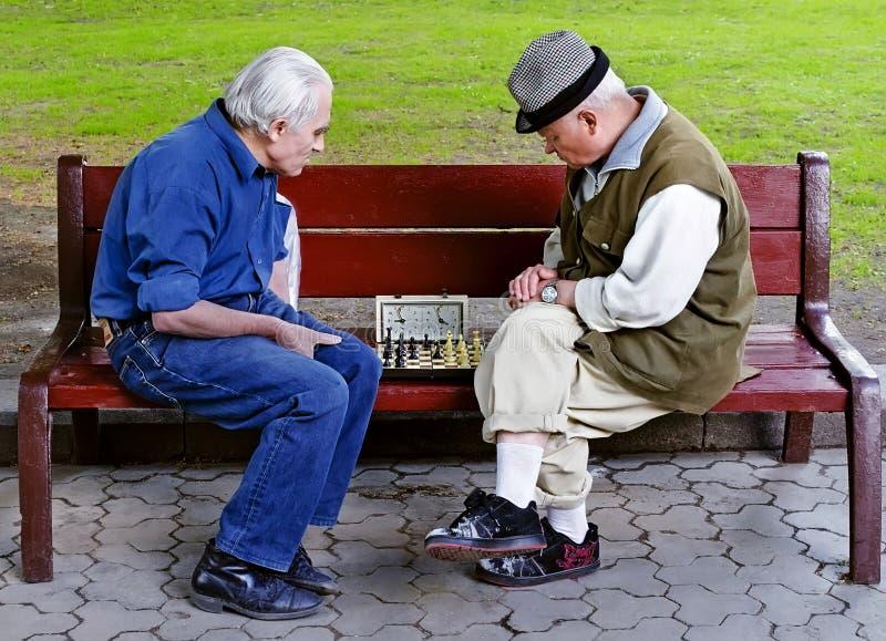 Scacchi del gioco della gente più anziana su un banco fotografia stock