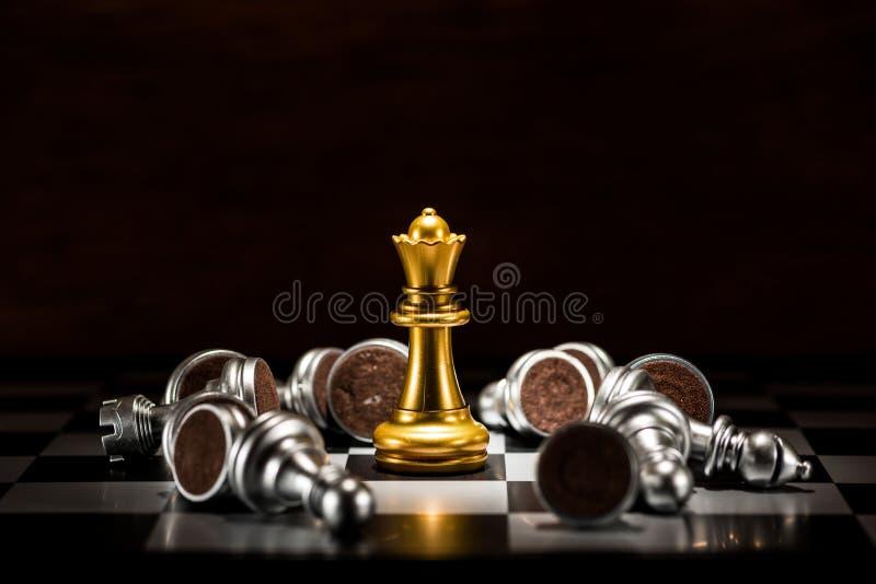 Scacchi della regina dell'oro circondati da una serie di scacchi d'argento caduti p fotografia stock libera da diritti