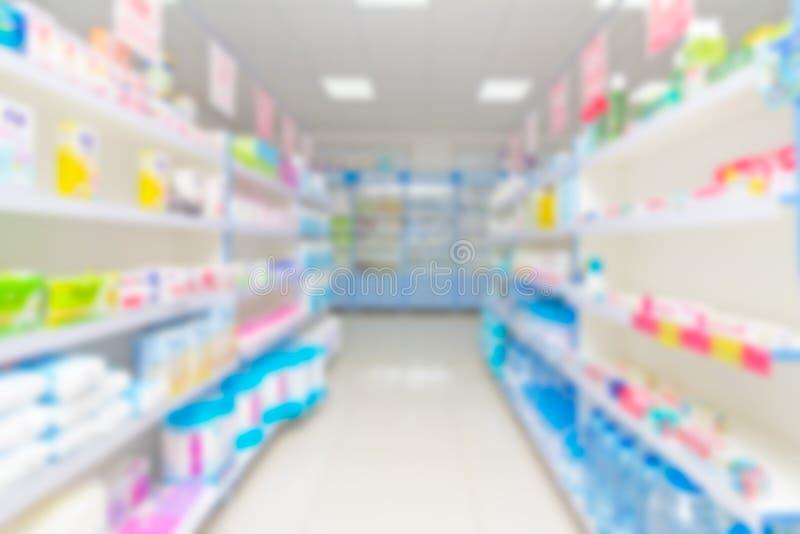 Scaffale astratto della sfuocatura del fondo con le medicine ed altre merci in farmacia fotografia stock libera da diritti
