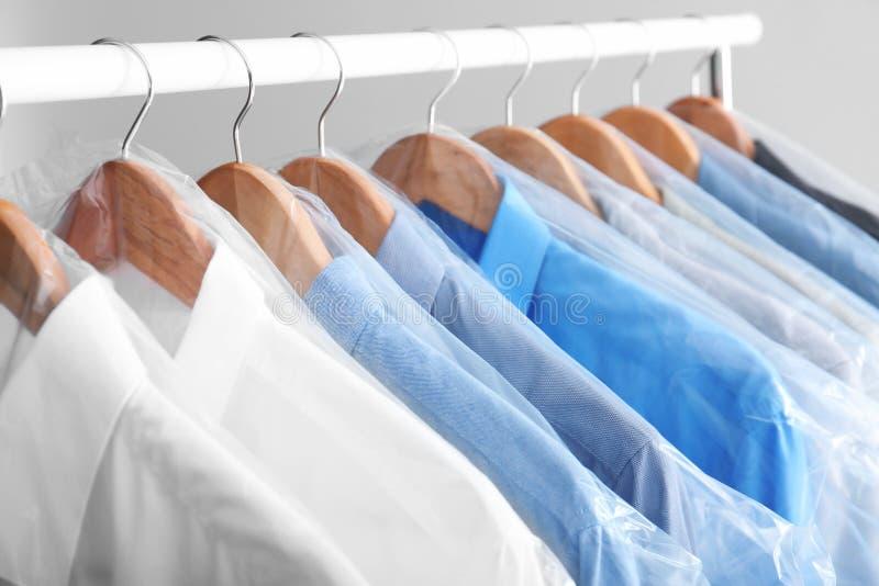 Scaffale con i vestiti puliti sui ganci fotografia stock