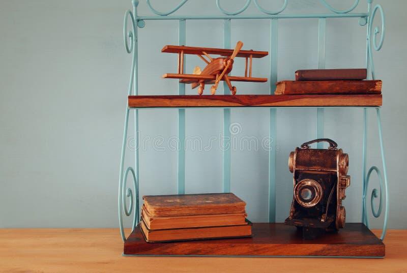 Scaffale d'annata con il vecchio giocattolo piano di legno, i libri e la macchina fotografica decorativa fotografie stock