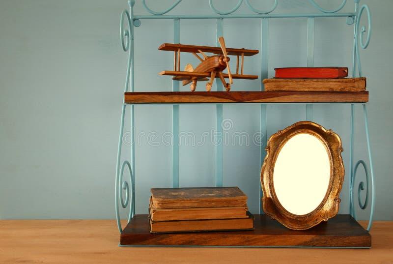 Scaffale d'annata con il vecchio giocattolo piano di legno, i libri e la struttura in bianco della foto fotografia stock