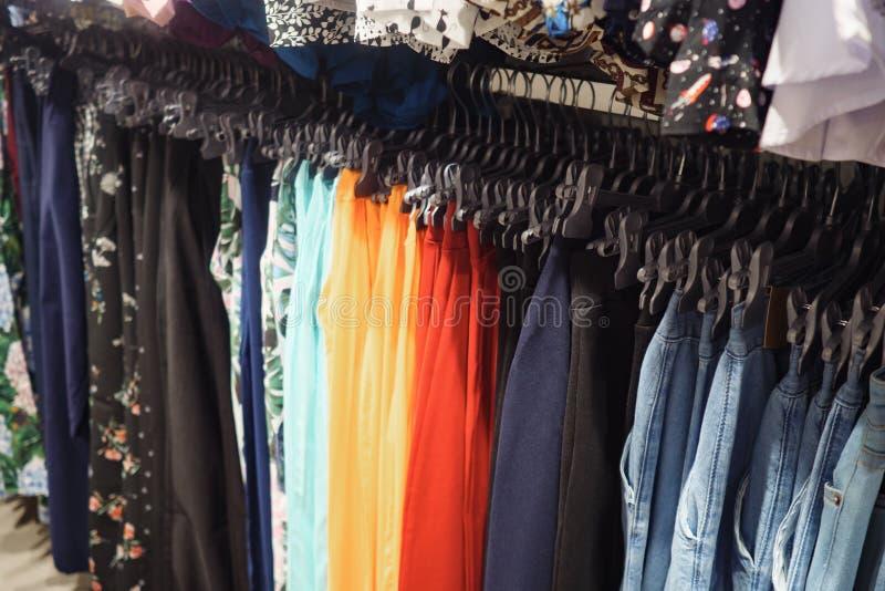 Scaffale del metallo con i ganci dei pantaloni alla moda variopinti in negozio contemporaneo immagine stock libera da diritti