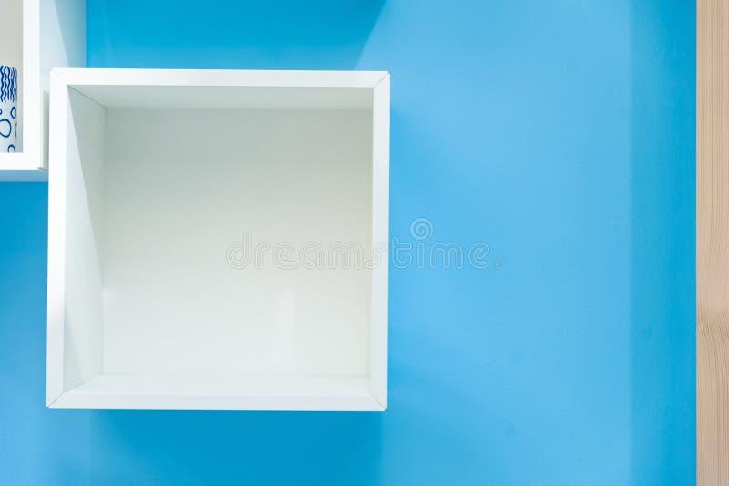 Scaffale della scatola bianca isolato su fondo blu fotografia stock
