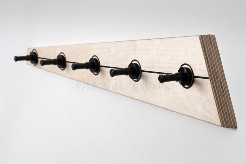 Scaffale di legno del cappotto con cinque pioli neri di plastica sulla parete bianca immagine stock