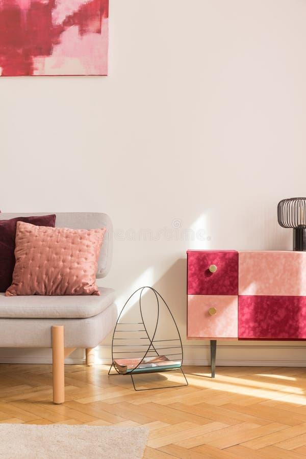 Scaffale di rivista operato fra Borgogna alla moda ed il sofà alla moda grigio rosa pastello e del gabinetto con il cuscino immagini stock
