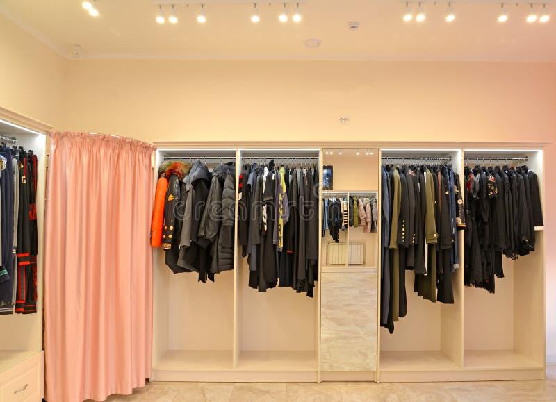 Scaffali con i vestiti e una stanza adatta una cabina in negozio immagine stock libera da diritti