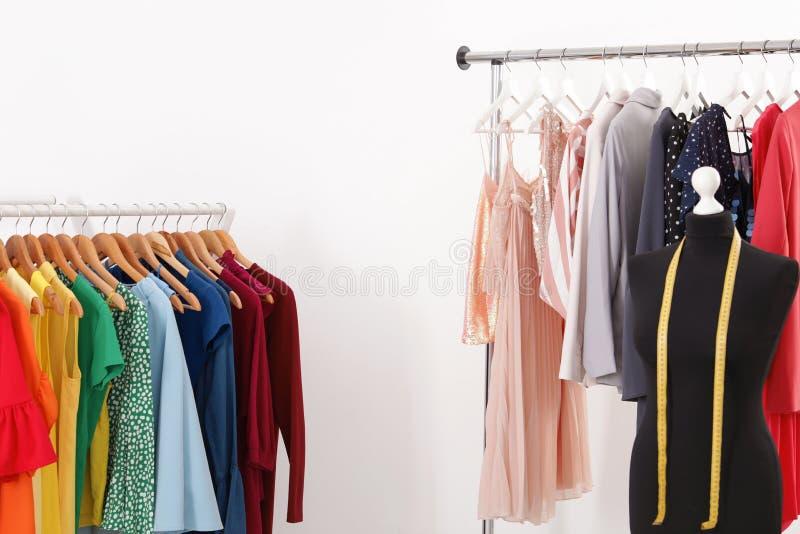 Scaffali con la raccolta dei vestiti d'avanguardia su fondo bianco immagine stock libera da diritti