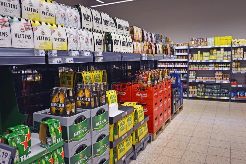 Scaffali con le casse della birra e pacchetti malati nel supermerket tedesco immagine stock