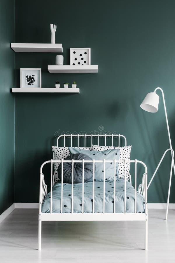 Scaffali con le decorazioni e una lampada di pavimento sopra un bianco, metallo f fotografia stock