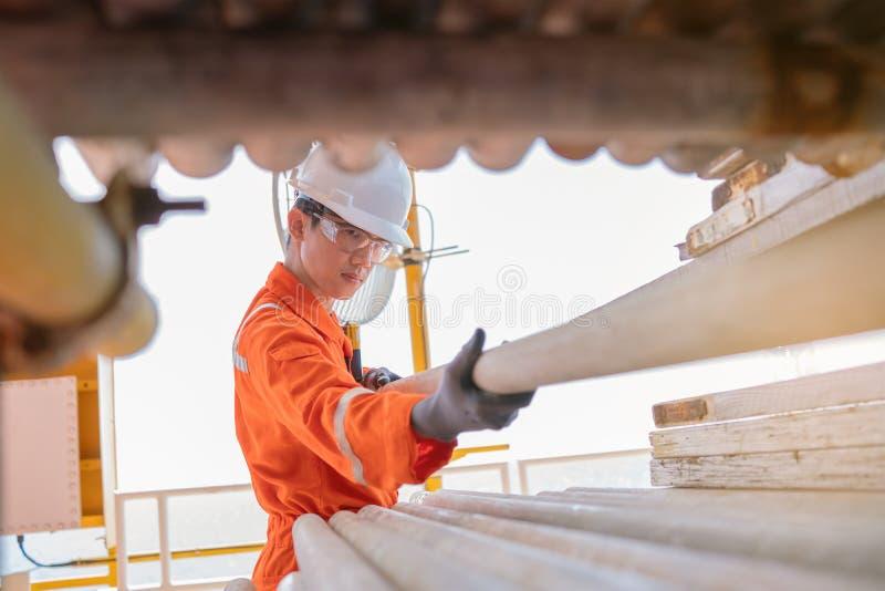 Scaffolder tirando andamios en rack para trabajos de construcción en plataformas de procesamiento de gas y petróleo mar adentro fotografía de archivo libre de regalías
