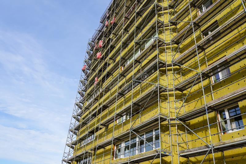 Scaffolding arround the house to install thermal insulation of the apartment building facade. Blue sky background stock photography