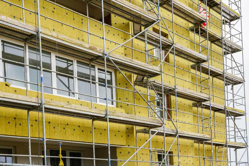 Scaffolding arround the house to install thermal insulation of the apartment building facade. Blue sky background royalty free stock image
