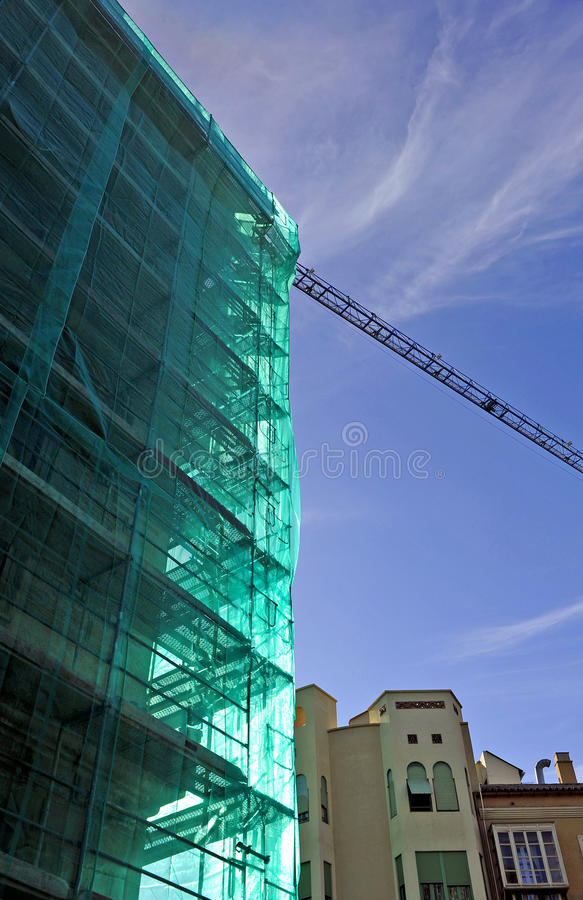 Scaffolding and cranes in a building under construction. Tarpaulins and green nets protecting the scaffolding on the facade of a building under construction royalty free stock images