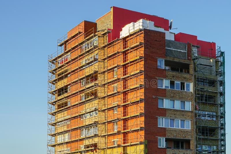 Scaffolding before installation of the thermal insulation of the apartment building facade. Against a blue sky stock photo