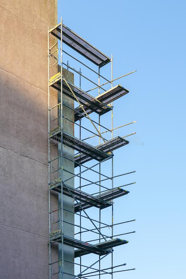 Scaffolding before installation of the thermal insulation of the apartment building facade. Against a blue sky royalty free stock photography