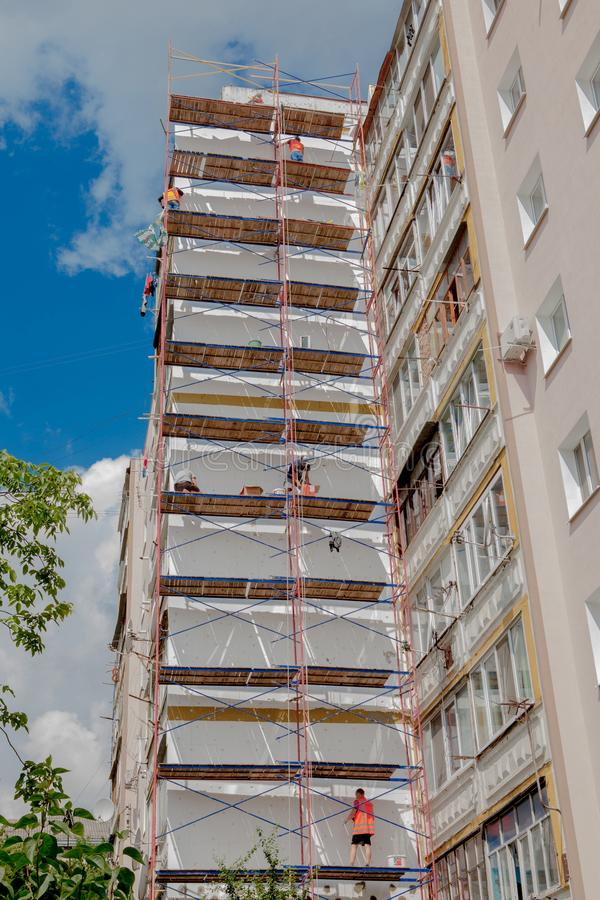 Scaffolding on a multistory building. Warming of the outer wall panel. A working man isolates the walls of a multistory building.  stock photography