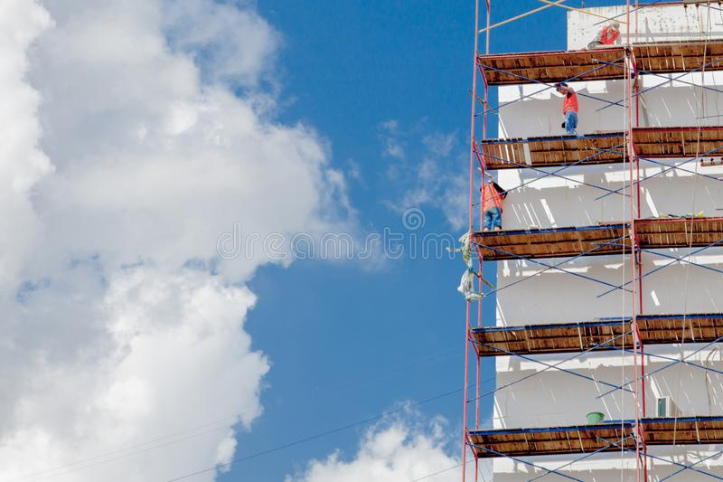 Scaffolding on a multistory building. Warming of the outer wall panel. A working man isolates the walls of a multistory building.  royalty free stock image