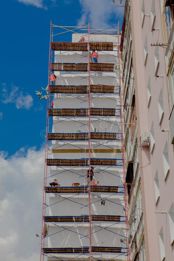 Scaffolding on a multistory building. Warming of the outer wall panel. A working man isolates the walls of a multistory building.  royalty free stock photos
