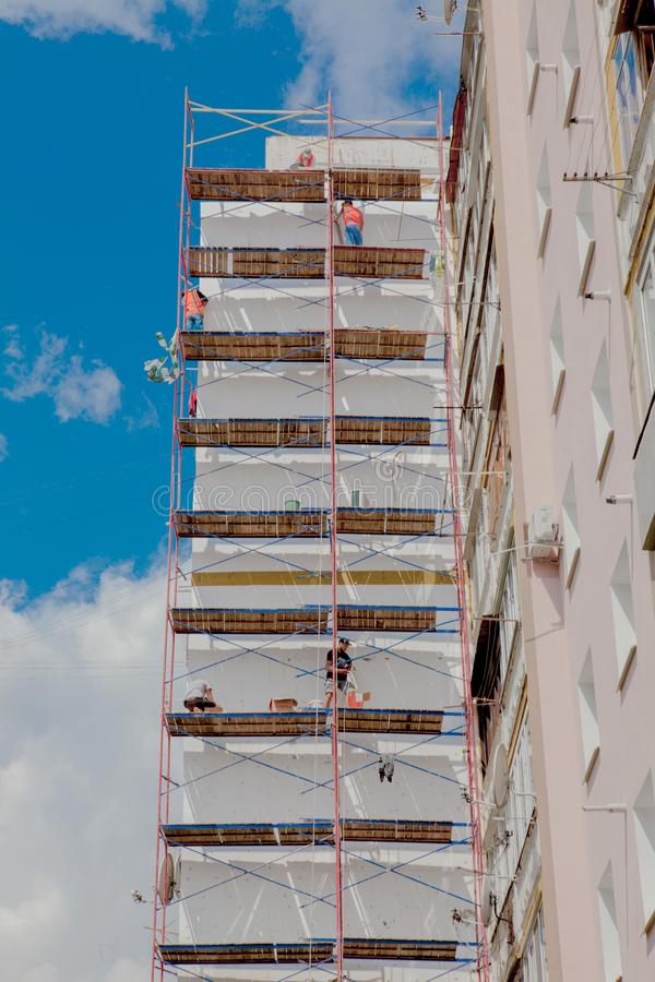 Scaffolding on a multistory building. Warming of the outer wall panel. A working man isolates the walls of a multistory building.  stock photos