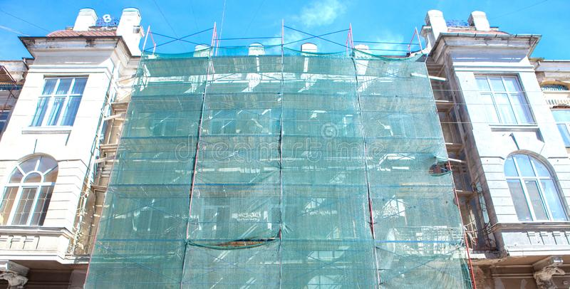 Scaffolding near a house under construction for external plaster works, high apartment building in city, white wall and window,. Yellow pipe stock image