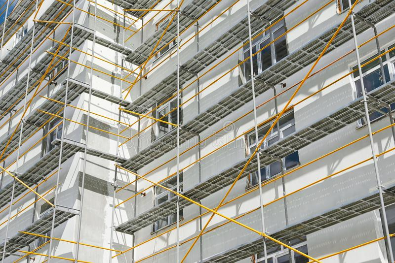 Scaffolding near a new house, building exterior, construction and repair industry, white wall and window, yellow pipe stock photos