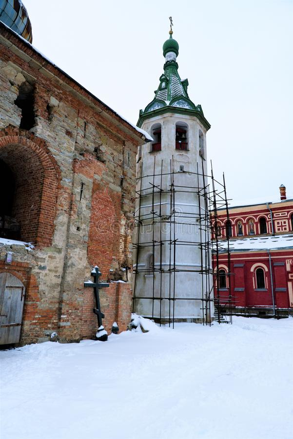 Scaffolding on the restored bell tower and a half-destroyed chapel in Nikolsky male monastery, Russia. royalty free stock photo