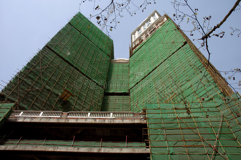 Scaffoldings. Green net covering scaffoldings of an under construction building royalty free stock photo