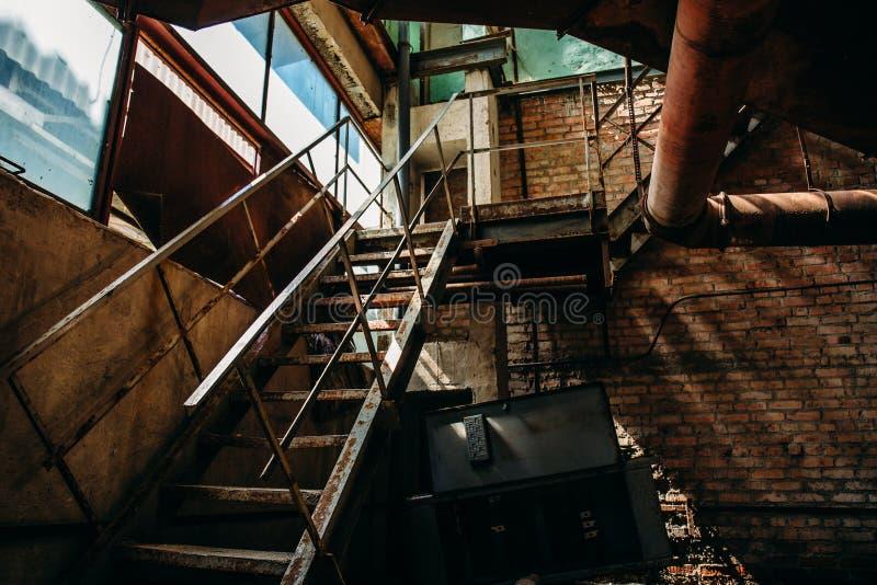 Scala arrugginita del ferro nel negozio del mattone della fabbrica abbandonata, dentro l'interno immagine stock libera da diritti
