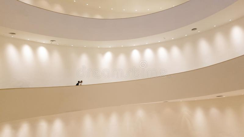 Scala a chiocciola bianca con la parete bianca con il riflettore e la gente immagini stock