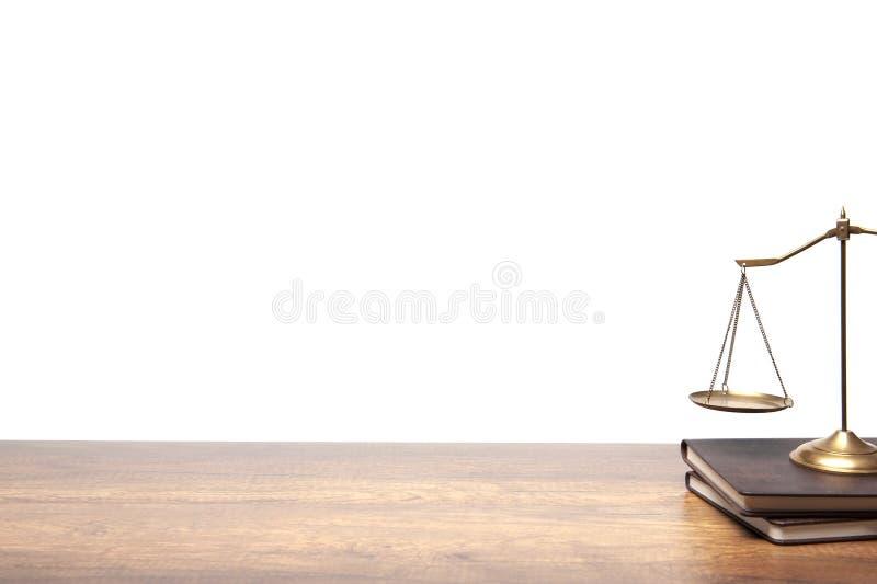 Scala d'ottone dell'equilibrio dell'oro disposta sulla tavola legna d'annata e del libro su fondo bianco fotografie stock libere da diritti