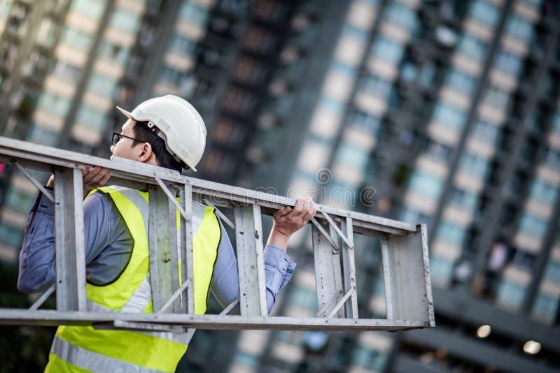 Scala di alluminio di trasporto dell'uomo del lavoratore di manutenzione immagini stock