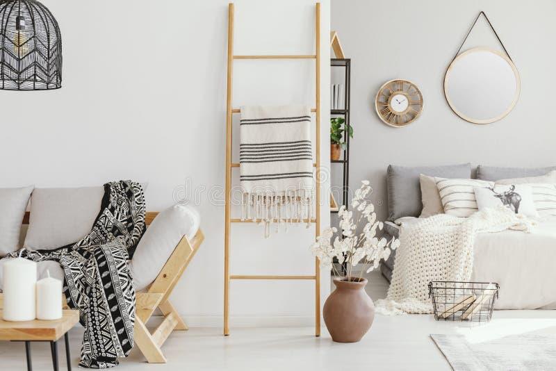 Scala di legno con la coperta fra il divano elegante con la coperta modellata ed il letto comodo con lettiera grigio chiaro immagini stock