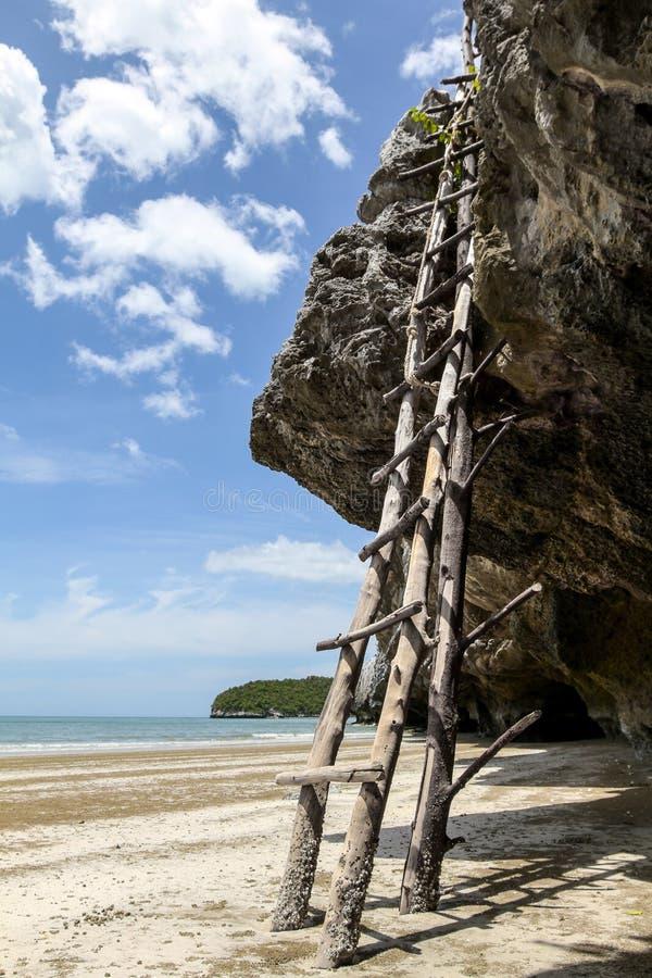Scala di legno da scalare fino alla roccia sulla spiaggia con la spiaggia ed il cielo nuvoloso blu nei precedenti fotografie stock