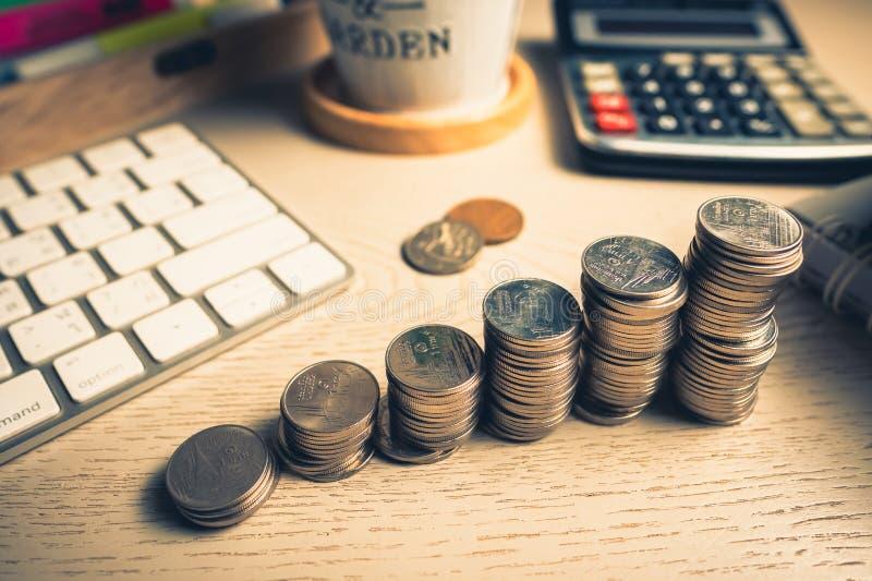 Scala di risparmio delle monete sullo scrittorio immagini stock