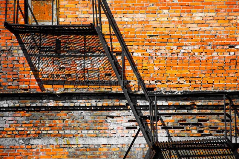 Scala industriale del metallo contro un fondo del muro di mattoni immagine stock