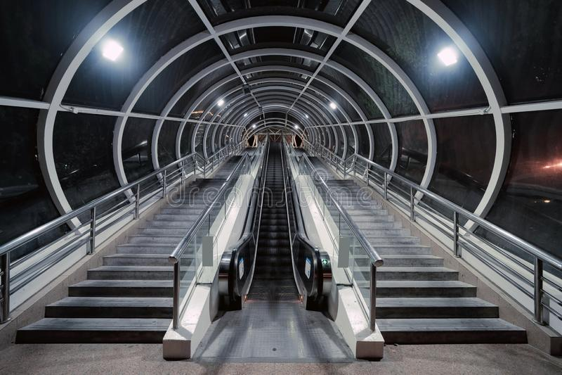 Scala mobile e tunnel in una stazione ferroviaria da trasferire nella città di Shanghai, Cina alla notte Struttura architettonica immagine stock