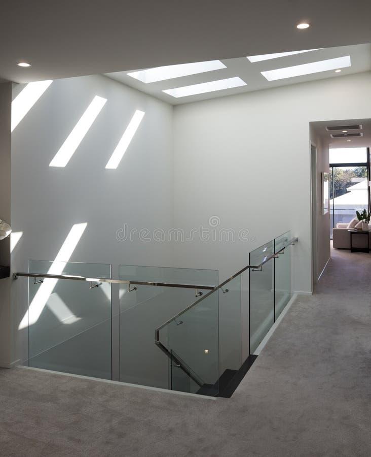 Scala moderna con luce solare luminosa attraverso le finestre del soffitto fotografie stock libere da diritti