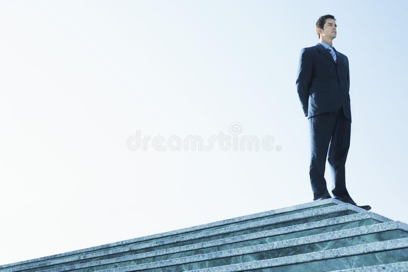 Scala sicura di Standing On Marble dell'uomo d'affari immagini stock