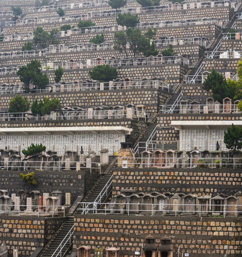Scala su un pendio di collina di numerose pietre tombali in un cimitero ammucchiato di Hong Kong immagine stock libera da diritti
