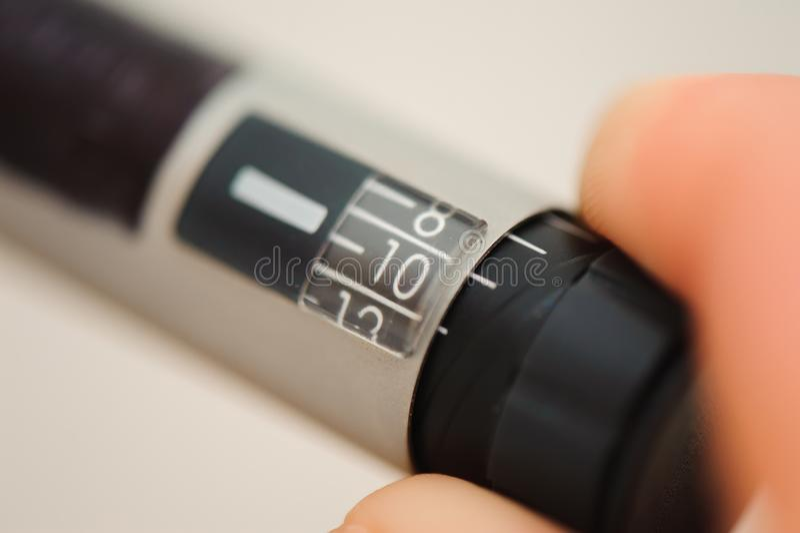 Scala sul fondo della penna dell'insulina, attrezzatura medica dall'iniezione di auto per i pazienti del diabete fotografia stock