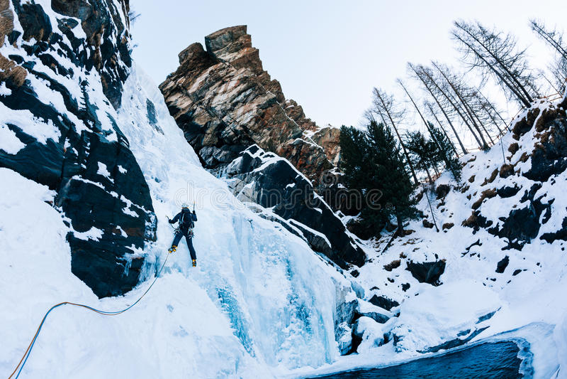 Scalata del ghiaccio: scalatore maschio su un icefall in alpi italiane fotografia stock
